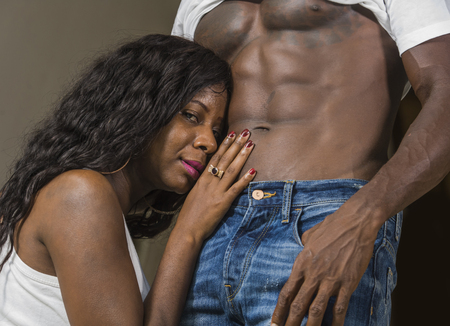 portrait of young attractive and happy black African American woman touching afro man ripped abdomen showing nude torso and six pack abdominals in fit sexy body worship 版權商用圖片