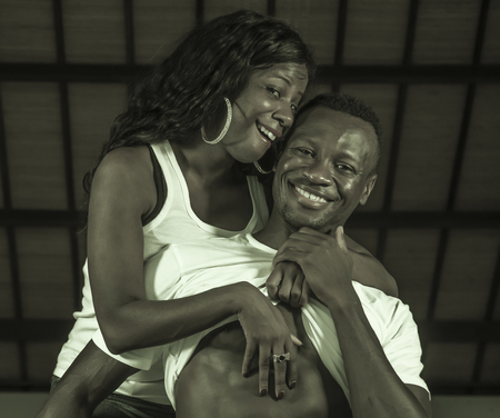 young happy and attractive black afro American couple the man showing sexy six pack abdomen and the woman playful proud and excited cuddling her lover in love and passion concept