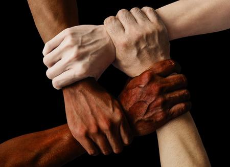 Multirassische Gruppe mit schwarzen afroamerikanischen, kaukasischen und asiatischen Händen, die sich gegenseitig am Handgelenk in Toleranz, Einheitsliebe und Antirassismuskonzept auf schwarzem Hintergrund halten