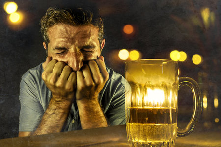 young desperate and depressed alcoholic man drinking beer wasted and drunk failing resisting to drink in bar pub at night falling into alcohol abuse in addiction and alcoholism problem Stock Photo