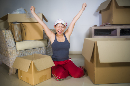 young beautiful and happy Asian Korean woman excited at home living room floor unpacking belongings from cardboard boxes moving to new apartment in first house and property investment concept Фото со стока