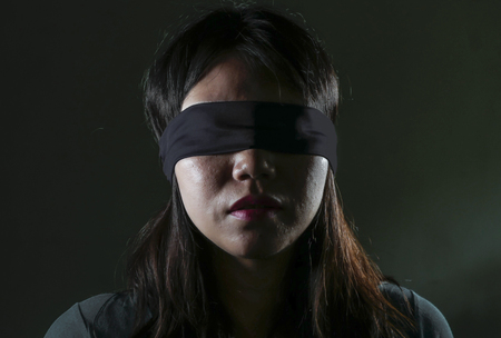 young scared and blindfolded Asian Korean teenager girl lost and confused playing dangerous internet viral challenge isolated on dark background under edgy and dramatic studio light Stockfoto