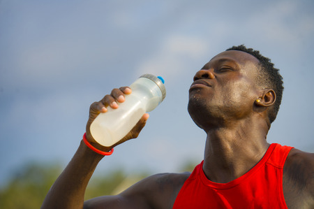 young handsome and attractive black afro American sport man tired and thirsty after running workout holding bottle drinking water or isotonic energy drink recovering in hydration concept