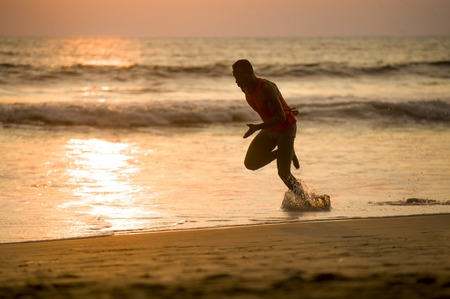 silhouette of young attractive fit athletic and strong black African American man running at sunset beach training hard and sprinting on sea water in professional athlete and runner workout
