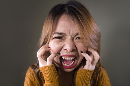 jeune femme coréenne asiatique folle désespérée et contrariée criant effrayée et anxieuse ressentant de la colère et de la douleur isolée sur fond sombre sur une expression de visage de douleur dramatique dans le concept de dépression Banque d'images
