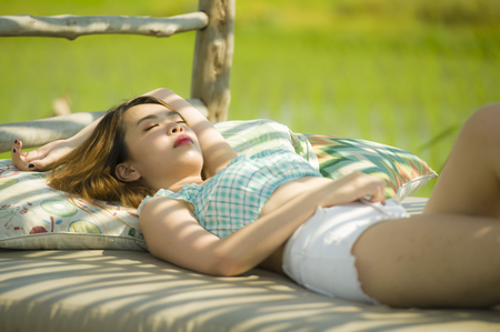 young beautiful and sexy Asian Korean woman lying comfortable at holidays resort garden bed having sunbath tanning relaxed and chilled in Summer vacation and beauty concept Фото со стока