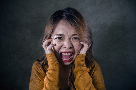 young crazy desperate and upset Asian Korean woman screaming scared and anxious feeling anger and pain isolated on dark background on dramatic pain face expression in depression concept Фото со стока - 114777672