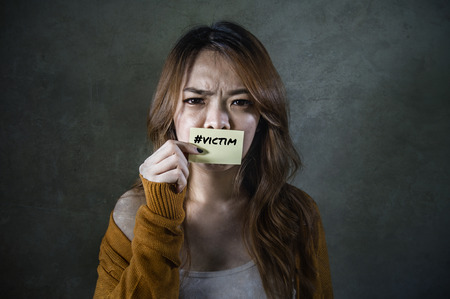 young sad and desperate Asian Korean student woman holding message paper as victim of abuse suffering domestic violence and bullying feeling helpless and harassed on isolated background 版權商用圖片