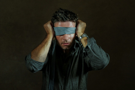 young lost and confused man blindfolded with necktie playing internet trend dangerous viral challenge with eyes blind acting doubtful guided by intuition isolated on dark background
