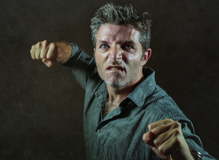 young upset and aggressive man in pub raising fist threatening throwing punch ready to fight as the violent thug troublemaker and furious wasted guy isolated on dark background