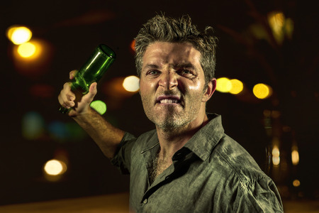 young upset and aggressive drunk man in pub at night holding beer bottle threatening ready to fight as the violent thug troublemaker in every bar and alcohol addict furious guy