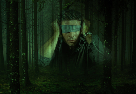 young confused and scared man blindfolded with necktie playing internet trend dangerous viral challenge with eyes blind lost in dark forest background guided by intuition Banque d'images