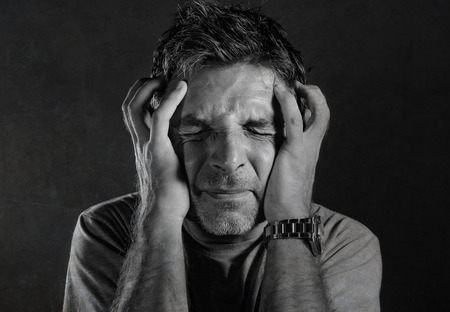 close up dramatic portrait of 30s to 40s desperate and depressed man in pain suffering anxiety and depression problem holding head with hands feeling overwhelmed isolated on black background