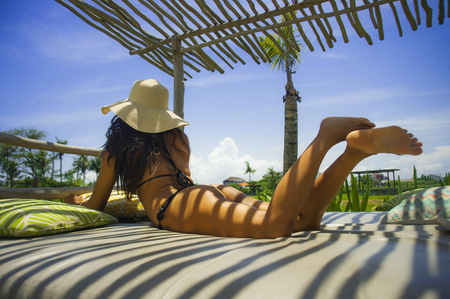 young sexy and beautiful woman in bikini chilled and relaxed lying on outdoors bed having suntan enjoying Summer holidays in tropical island background in vacations travel and attractive body concept