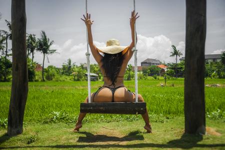 jeune femme séduisante et détendue avec un corps s'amusant sur une balançoire profitant d'un voyage de vacances sur une île paradisiaque tropicale portant un bikini et un chapeau d'été dans le concept de tourisme et de vacances