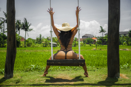 young attractive and relaxed woman with body having fun on swing enjoying holidays trip at tropical paradise island wearing bikini and Summer hat in tourism and vacation concept