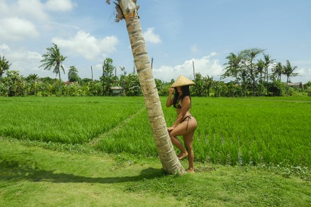 young sexy and happy Southeast Asian woman in tradition rural hat posing in bikini at beautiful rice field landscape in Asia tourism and Summer holidays travel concept Stockfoto
