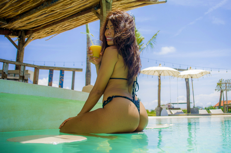 young sexy and attractive Asian woman in bikini at swimming pool bar drinking orange juice enjoying Summer holidays happy and relaxed at tropical luxury resort in Asia in paradise vacation concept