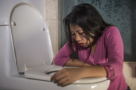 young drunk or pregnant Asian woman vomiting and throwing up in toilet WC feeling unwell and sick suffering stomach ache and nausea as pregnancy symptom or intoxicated in hangover 版權商用圖片 - 115323140