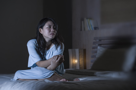 dramatic portrait of young beautiful and sad Asian Japanese woman crying desperate on bed awake at night suffering depression crisis and insomnia feeling pain and broken heart Stockfoto