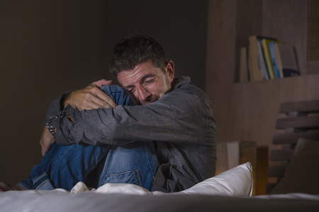 young crazy desperate and depressed man crying on bed suffering anxiety crisis and depression problem feeling overwhelmed and stressed late at night  in fetal position on dramatic light Stock Photo