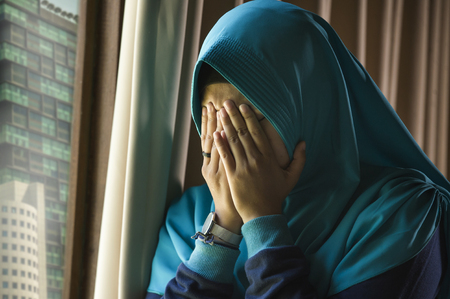 lifestyle portrait of young sad and depressed Muslim woman in Islam traditional Hijab head scarf at home window feeling unwell suffering depression crisis and anxiety problem crying helpless