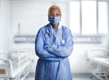 young attractive and confident black African American medicine doctor wearing face mask and blue scrubs standing corporate in health care work concept isolated at hospital room Banco de Imagens