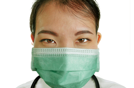 close up isolated portrait of young attractive and confident Asian Chinese medicine doctor woman in protective face mask and scrubs with stethoscope in hospital health care