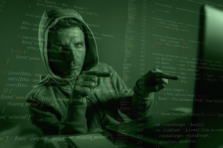 computer programmer man in hoodie hacking system entering code pointing to laptop hacking and decoding system data illegal access breaking password on cyber attack and security breach 스톡 콘텐츠