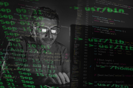 weird tidy and nerd hacker man in big glasses programming and hacking laptop computer system entering dangerous code  late night in the dark breaking password in programmer cyber attack