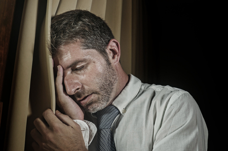 dramatic lifestyle portrait of young sad and depressed businessman in necktie feeling frustrated suffering depression and business problem leaning on window curtains late night at home office