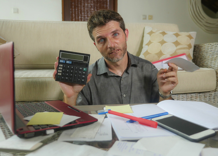 young stressed and worried man at home living room using calculator and laptop doing domestic accounting paperwork feeling overwhelmed on money tax expenses and financial status