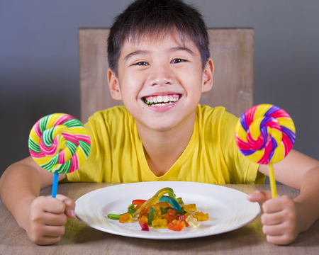 young happy and excited male kid smiling cheerful eating dish full of candy and lollipop sitting at table isolated on grey background in sugar addiction and abuse and sweet unhealthy nutrition 写真素材