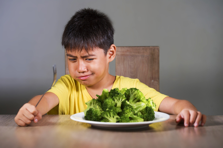 7 or 8 years old upset and disgusted Asian kid sitting on table in front of broccoli plate looking unhappy rejecting the fresh food in child hate green vegetables concept and healthy nutrition