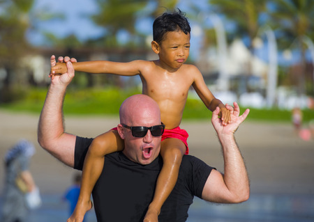 young happy Caucasian man and his mixed Asian ethnicity young son at tropical beach Summer holidays the child sitting on his father shoulders enjoying cheerful playing together