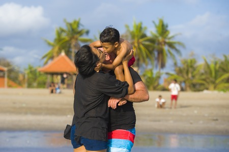 young happy and romantic mixed ethnicity couple Caucasian man and Asian Indonesian woman kissing and playing at tropical beach with little son on shoulders of his father on holidays trip Banco de Imagens