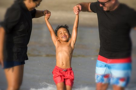 young happy mixed ethnicity couple Caucasian man and Asian Indonesian woman playing at tropical beach with little son the parents raising up the child above the sea water having fun in holidays trip