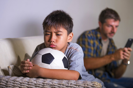 young sad and bored child at home couch feeling frustrated and unattended waiting his father for playing football while man networking on mobile phone as internet addict father neglecting son