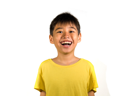 portrait of young happy and excited child smiling and laughing cheerful wearing yellow t-shirt isolated on white background in kid happiness and joyful face expression concept