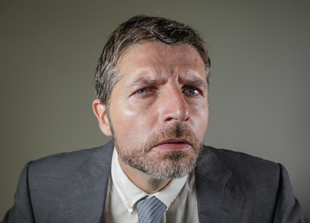 close up face portrait of young angry and unhappy businessman in suit and tie looking serious and inquisitive posing bossy and cool as if wondering or listening to employee excuses in anger Stock Photo