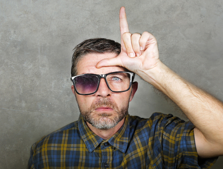30s or 40s unshaven sad and ridiculous man in weird broken nerdy glasses doing loser sign with hand and fingers on his forehead with funny depressed expression in unsuccessful geek concept