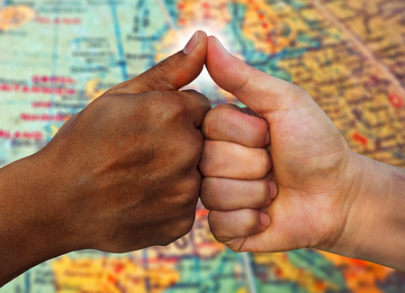 multiracial hands together one hand African American and another Asian or Caucasian touching thumbs as team in promise sign of mutual trust representing world diversity respect