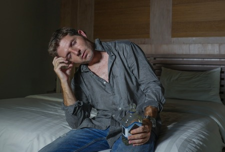 young depressed and wasted drunk man drinking vodka bottle at home sitting on bed thoughtful and confused as alcoholic suffering alcoholism problem and alcohol addiction in dramatic light