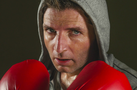 close up face portrait of young attractive and fierce looking man in boxing gloves posing in defense boxer stance isolated on dark background in sport and fitness exercise workout 免版税图像