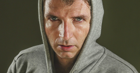 close up sweaty face portrait of young attractive and fierce looking man wearing hoodie posing in aggressive and defiant attitude isolated on dark background in sport and fitness concept
