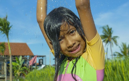 young happy and carefree beautiful child 7 or 8 years old outdoors having shower at a beautiful rice terrace playful under the water wearing cute girl swimsuit enjoying holidays and nature free Stok Fotoğraf