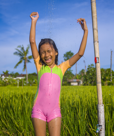 young happy and carefree beautiful child 7 or 8 years old outdoors having shower at a beautiful rice terrace playful under the water wearing cute girl swimsuit enjoying holidays and nature free 스톡 콘텐츠