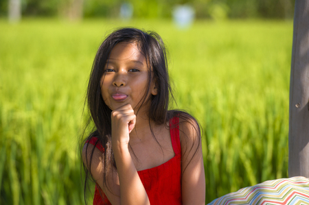 outdoors lifestyle portrait of beautiful and sweet young girl happy posing doing playful faces tongue out, the child dressed in a red dress isolated on green field landscape background Stock fotó