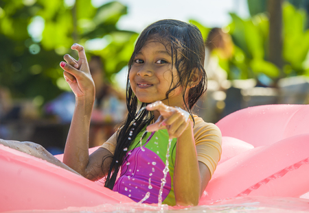 lifestyle outdoors portrait of young happy and cute female child having fun with inflatable airbed in holidays resort swimming pool smiling carefree and cheerful in young girl vacations concept