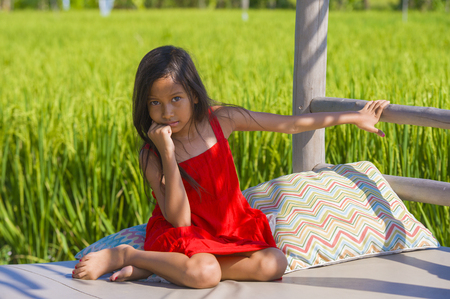 sweet shy and beautiful 7 or 8 years old child in cute red Summer dress having fun outdoors smiling cheerful at rice field in young girl enjoying holidays and nature concept